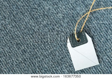 View of Handmade Blue Wool Fabric Texture with diagonal Direction of Threads and blank Vintage Jeans Price Tag on natural hempen thread for Business and Retail Backgrounds
