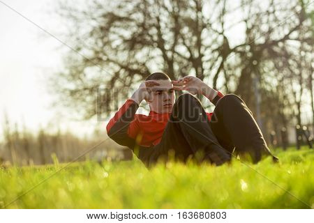 Young sportsman working-out in a park, doing a series of crunches