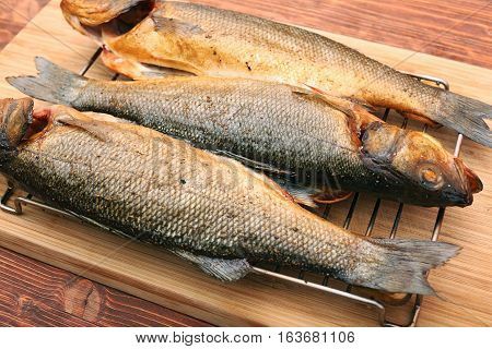 Smoked sea bass on a wooden table background