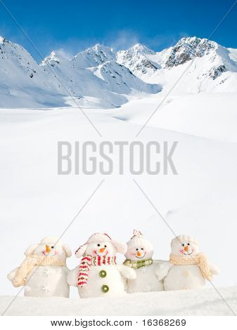 Happy snowman friends in mountains (copy space)