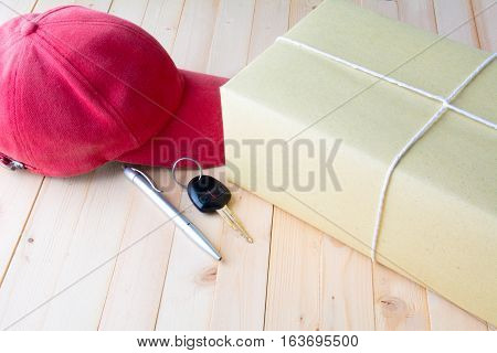 The red cap, parcel post, white paper, pen and key of car on bark table