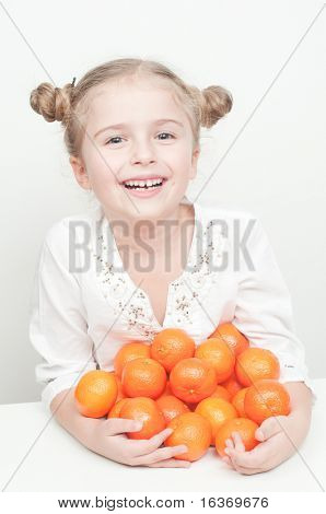 Healthy food - little girl with  mandarin fruits