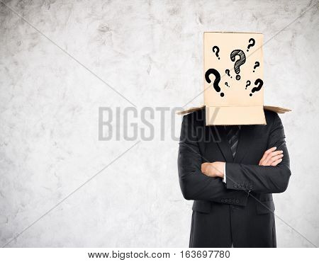 Businessman with folded arms and cardboard box with question marks covering head on concrete background. Confusion concept
