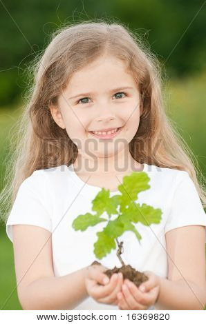 Seedling - little girl and young plant of a oak