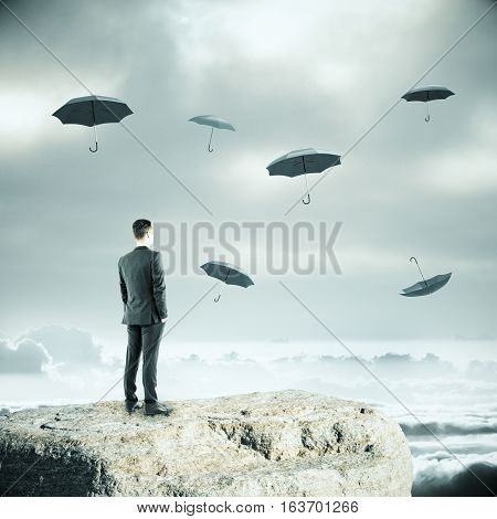 Thoughtful businessman standing on cliff and falling umbrellas on dull sky background. Safety concept