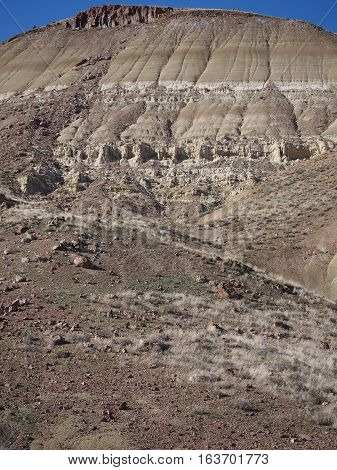 A layered hill of several colors and rugged texture in the Painted Hills Unit of the John Day Fossil Beds in Eastern Oregon on a sunny Spring day.