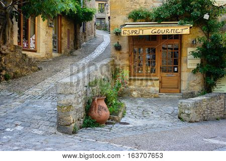 Beynac-et-Cazenac France - August 25 2015: Typical French townscape with a gourmet store front and cobblestone streets in the traditional town Beynac-et-Cazenac along Dordogne river in Perigord region France.