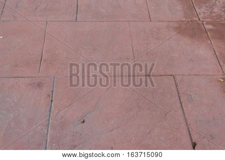 Stamped concrete floor outdoor pavement, mimics colors and textures of material pavers, red square pattern detail, appearance of natural stone