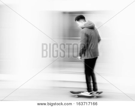 Young man riding on the skateboard, photo with movement