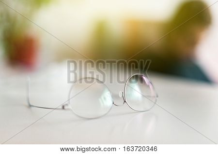 Elegant eyeglasses spectacles with thin titanium rim on office table with office employee silhouette working in the background