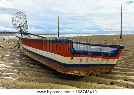 Fishing boats with the landing net in Tanjung Aru jetty, Labuan island, Malaysia fishing village with blue sky and clouds at low tide.