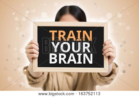Train Your Brain Text On Chalkboard In Child Hands.