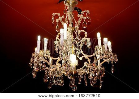 Crystal glass chandeliers and sparkling candle on burgundy background