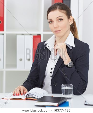 Beautiful thoughtful business woman sitting at office workplace looking into the camera. Serious business and partnership job offer financial success certified public accountant concept