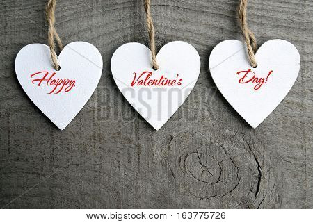 Happy Valentines Day background. Decorative white wooden hearts on grey rustic wooden background with copy space.Selective focus.Winter holidays,Valentine's Day concept.
