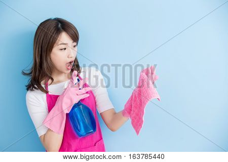 beauty housewife take rag and detergent feel surprise isolated on blue background asian
