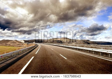 Asphalt and travel concept.Road and sunset.Empty highway,mountain landscape and cloudy sky.Road and car travel concept
