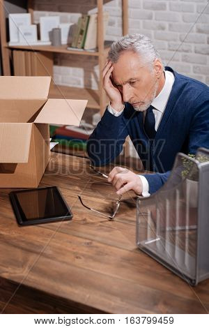This might be the very end. Depressed doubtful elderly man putting thought into all his work during his career while sitting at his table with things packed ready for leaving