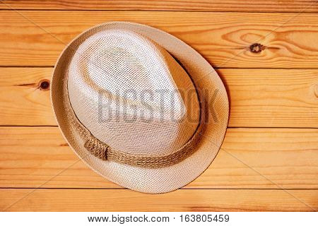 White hat decorated with ribbon on wooden background