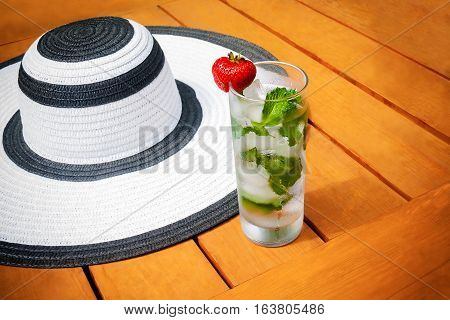 Glass of water with ice and mint and summer hat on wooden background. Selective focus
