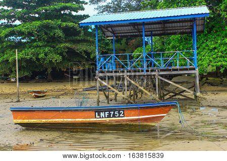 Labuan,Malaysia-Jan 3,2017:Fishing boat in Tanjung Aru jetty,Labuan island,Malaysia, fishing village with blue sky and clouds at low tide.