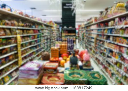 Supermarket blur background with miscellaneous product shelf useful for shopping concepts