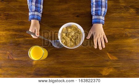 Cute little kid eating corn flakes on breakfast and drinking orange juice