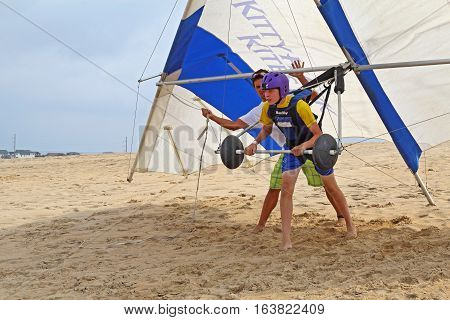 NAGS HEAD NORTH CAROLINA - JULY 29 2013: Student prepares for takeoff with an instructor from the Kitty Hawk Kites Hang Gliding School on the sand dunes of Jockeys Ridge State Park on the Outer Banks