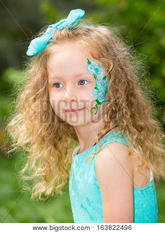 Beautiful happy girl kid with aqua make-up on birthday in park. Celebration concept and childhood love