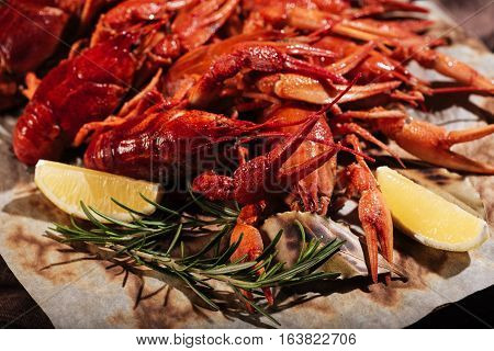Delicious and spicy. Close up of crayfishes with lemon and rosemary lying on a table while being put on a pita in a restaurant.