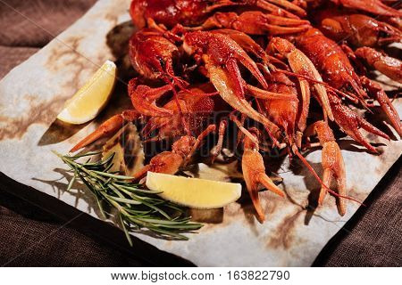 Perfect view. Crayfishes with lemon and rosemary lying on pita while being put on a table in a restaurant.