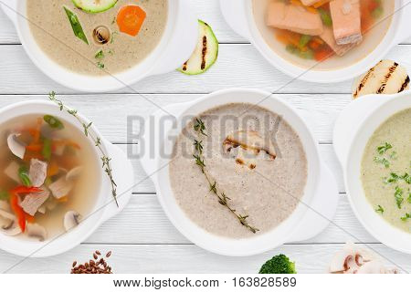 Set of different tasty soups on wooden table flat lay. Top view on variety of restaurant hot dishes. Worldwide cuisine, healthy food, buffet, lunch, menu concept