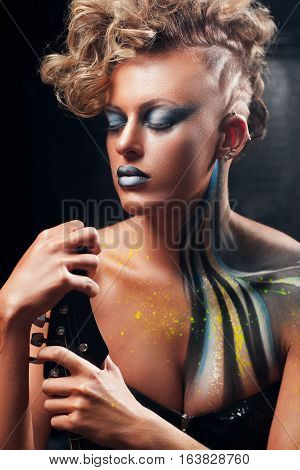 Punk woman posing with closed eyes portrait. Beautiful rocker girl with aggressive makeup, body art and hairstyle sitting with guitar. Subculture, lifestyle, hobby, expression, fashion concept