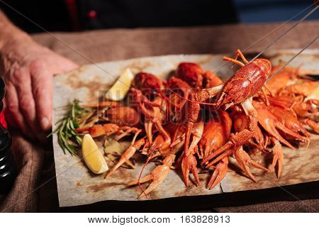 Presents from sea. Crayfishes standing on a table while being served on a pita and wooden tray in restaurant.