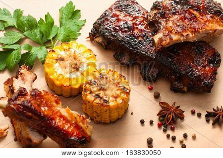 Barbecue spare ribs with corn on wood. Appetizing hot grilled meet with vegetable meal. Junk food, beer snack, restaurant menu concept