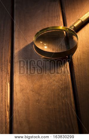 Magnifying glass with shadow under beam of light on wooden background.