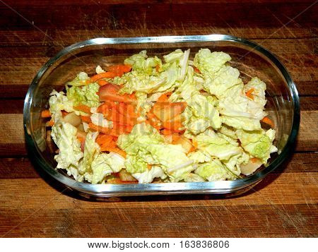 in a transparent plate on a wooden chopping board salad of chopped Chinese cabbage, grated carrots and orange sliced boiled potatoes on a horizontal surface top view