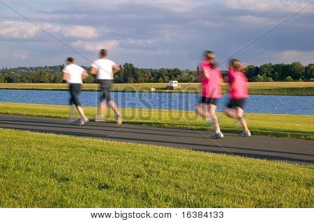 Women joggers out for a summer's evening run, deliberate motion blur.