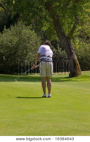 A male golfer having just taken his putt, slight motion blur on the club.