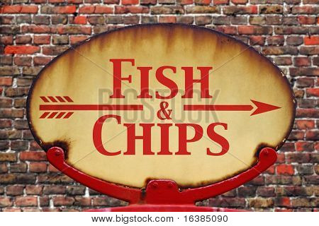 A rusty old retro arrow sign with the text Fish and chips