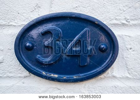 a blue street number sign with the number 34