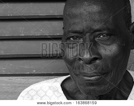 GHANA, WEST AFRICA - OCT 25, 2015: Elderly Man gazing into the camera while waiting in line for a health checkup at the missions clinic in Accra.