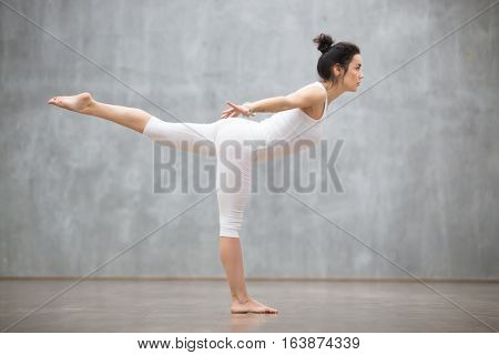 Profile portrait of beautiful young woman wearing white tank top working out against grey wall, doing yoga or pilates exercise. Standing in variation of Warrior three pose, Virabhadrasana. Full length