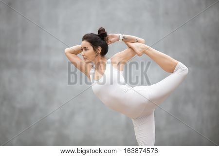 Portrait of beautiful young woman wearing white sportswear working out against grey wall, doing yoga or pilates exercise. Standing in Natarajasana, Lord of the Dance pose