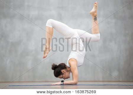 Portrait of beautiful young woman wearing white sportswear working out against grey wall, doing yoga or pilates exercise. Handstand with bending legs, variation of Pincha Mayurasana. Full length shot