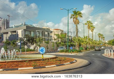 Rishon LeZion Israel-May 27 2016: Roundabout with small fountain on Heil HaTothanim Street. Tree private cars driving on the street with green palms. 2-story houses are seen in left site. This picture is taken in bright sunny day