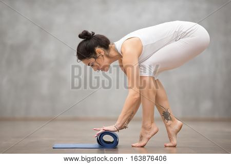 Attractive smiling young woman wearing white sportswear with beautiful tattoos folding blue yoga or fitness mat after working out at home or in club. Full length photo. Healthy life concept