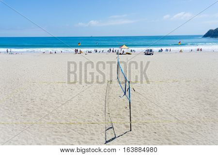 Mount Maunganui, New Zealand - December 21, 2016; ocean-beach with people enjoying summer and beach activities beyond beach volleyball net lifesavers flags and shelter.