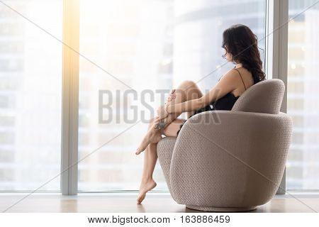 Back view of young barefoot model woman sitting in modern armchair, looking at city after waking up at morning, spend time relaxing, relaxation before bedtime, after long day. Skincare, beauty concept