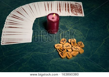 Composition of esoteric objectscandleCards and wooden runes used for healing and fortune-tellingon green backgroundvintage style.